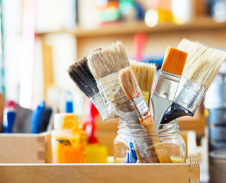 44384575 - paint brushes and crafting supplies on the table in a workshop.